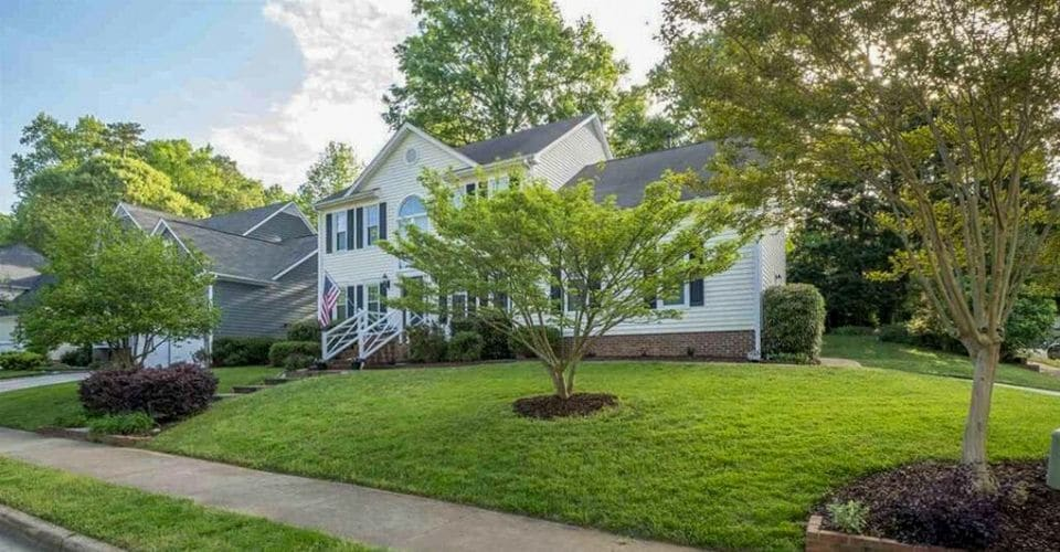 A home with a thick, green lawn from a lawn aeration and over seed service.