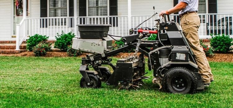 Commercial stand-on aerator performing service on residential lawn.