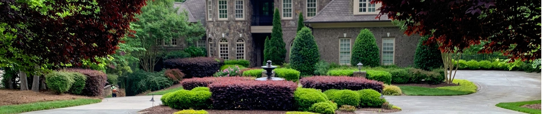 Estate in Raleigh, NC with a ECM Landscaping and Lawn Care employee finishing up a lawn service.