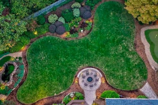 Aerial view of a dark green lawn surrounded by landscaping.