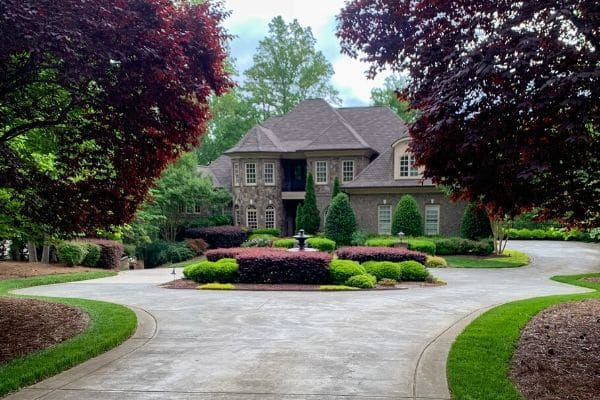 Estate with detailed landscaping requiring professional year-round maintenance.