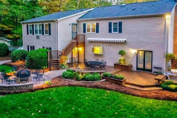 Back of home in Raleigh with a deck, landscaping, and fire pit.